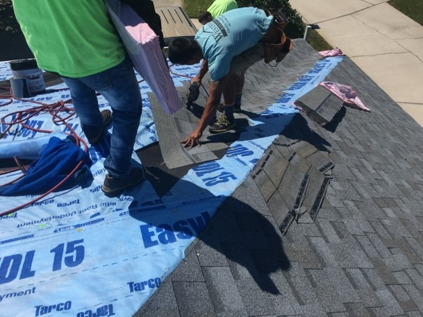 Roofing contractors installing asphalt shingles over blue underlayment on a residential home.