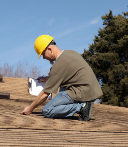 Roofing contractor kneeling on a roof while inspecting asphalt shingles for repairs