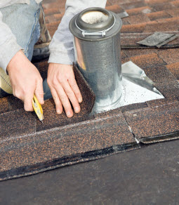 A close-up view of a roofer's hands while he cuts shingles to fit around ventilation on a residential roof