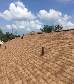 A close-up view of a newly repaired tan shingle roof on a home